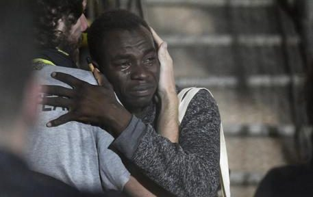 In this photo taken on Tuesday, Aug. 20, 2019 a man cries as he hugs a crew member after disembarking from the Open Arms rescue ship on the Sicilian island of Lampedusa, southern Italy. An Italian prosecutor ordered the seizure of a rescue ship and the immediate evacuation of more than 80 migrants still aboard, capping a drama Tuesday that saw 15 people jump overboard in a desperate bid to escape deteriorating conditions on the vessel and Spain dispatch a naval ship to try to resolve the crisis. (ANSA/AP Photo/Salvatore Cavalli) [CopyrightNotice: Copyright 2019 The Associated Press. All rights reserved.]
