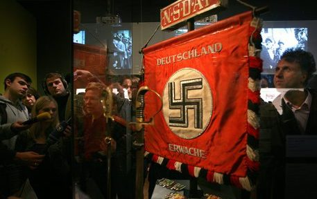 epa02392958 Journalists examine a flag showing a swastika, which is displayed during the preview to the exhibition 'Hitler and the Germans. Nation and Crime' at the German Historical Museum in Berlin, Germany, 14 October 2010. The exhibition opens 15 October 2010 and  runs until 06 February 2011.  EPA/STEPHANIE PILICK