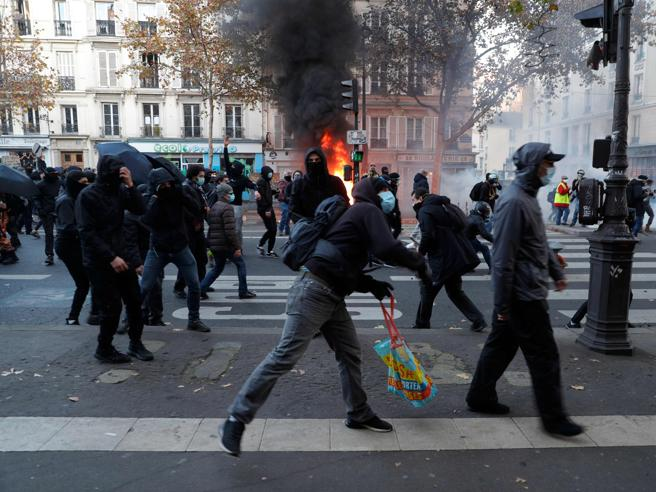 """A person dressed in black throws a projectile in Paris on November 28, 2020 during a protest against the """"global security"""" draft law, which Article 24 would criminalise the publication of images of on-duty police officers with the intent of harming their """"physical or psychological integrity"""". - Dozens of rallies are planned on November 28 against a new French law that would restrict sharing images of police, only days after the country was shaken by footage showing officers beating and racially abusing a black man. (Photo by GEOFFROY VAN DER HASSELT / AFP)"""
