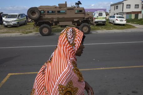 epa07770093 A woman walks past South African National Defence Force (SANDF) soldiers in armored vehicles on the Cape Flats in Mitchells Plain, Cape Town, South Africa, 12 August 2019. According to South African Minister of police General Bheki Cele there have been 1004 arrests during Operation Lockdown over the past month. Operation Lockdown is a joint operation between the South African Police Services (SAPS) and the South African National Defence Force (SANDF) aimed at tackling the alarming and rising number of gang related crimes on the Cape Flats. The Cape Flats is an area where non-white South Africans from Cape Town were sent by forced removal as part of the group areas act during the apartheid era. 50 years on from this the area has become a crime hotspot in the country with rampant gang activity and high numbers of murders and killings of innocent members of the community. Over 1300 SANDF soldiers have been deployed to assist the police with this operation.  EPA/NIC BOTHMA