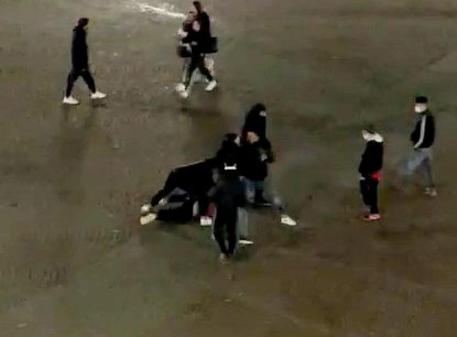 Un'immagine di una delle due risse in strada a Melegnano (Milano), tra bande di giovanissimi, 17 gennaio 2021. E' accaduto venerdì 15 e sabato 16 nella piazza antistante il castello mediceo. I residenti della zona sono stati attirati alle finestre dal rumore e hanno potuto vedere una ventina di ragazzi che, per lo più senza mascherine, si picchiavano urlando e rincorrendosi. ANSA/FLAVIA MAZZA