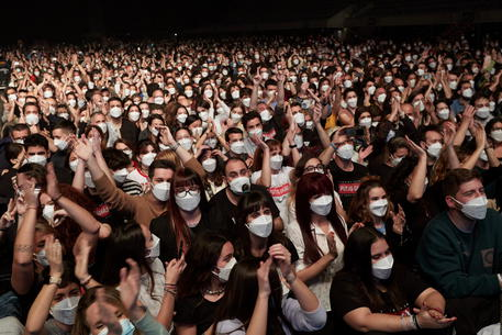 epa09101859 Members of the audience react as Spanish band Love of Lesbian performs on stage in front of 5,000 people at the Palau Sant Jordi arena in Barcelona, Catalonia, Spain, 27 March 2021. This is the first crowded concert in Spain since the beginning of the COVID-19 coronavirus pandemic a year ago. People had to go through a PCR test and were given FPP2 masks before entering the test concert venue.  EPA/Alejandro Garcia
