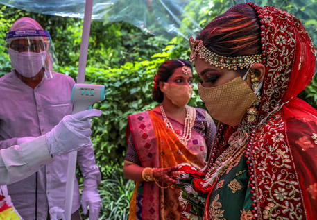epa08508482 Indian security person of wedding hall checks the body temperature of a Hindu bride who wears a fancy protective face mask upon arrival at the venue of her wedding in Mumbai, India, 25 June 2020. According to state government guidelines, a maximum of 25 people from groom and bride side, a total of 50, are allowed to attend the wedding ceremonies due to the coronavirus pandemic and related restrictions.  EPA/DIVYAKANT SOLANKI  ATTENTION: This Image is part of a PHOTO SET