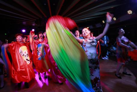epa06037476 (31/34) Parents of Chinese LGBTs (lesbian, gay, bisexual and transgender) and volunteers of the Parents and Friends of Lesbians and Gays (PFLAG) China organisation dance with rainbow scarves and colourful costumes during a closing ceremony for the 10th National PFLAG conference held on a cruise in open seas on route back to Shanghai China, 17 June 2017. About 800 members of the Chinese LGBT (lesbian, gay, bisexual and transgender) community and their parents spent four days on a cruise trip organised by Parents and Friends of Lesbians and Gays (PFLAG) China, a grassroots non-government organisation, celebrating the 10th anniversary of the organisation. It aims to promote coexistence among homosexuals and their families.  EPA/HOW HWEE YOUNG CHINA OUT ATTENTION: For the full PHOTO ESSAY text please see Advisory Notice epa06037443