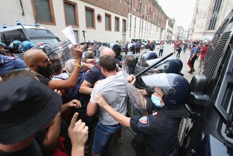 Scontri con le forze dell'ordine durante la manifestazione dei no vax in piazza Duomo, Milano, 25 settembre 2021. ANSA/PAOLO SALMOIRAGO